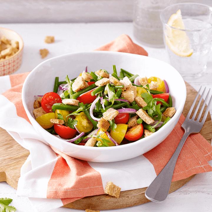 Eine Schale mit Tomaten-Bohnen-Salat und Knusper-Croûtons